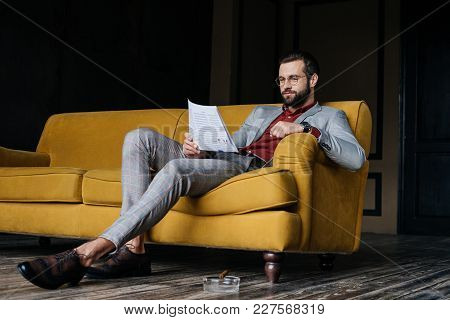 Stylish Man Reading Newspaper And Sitting On Couch, Ashtray With Cigar On Floor
