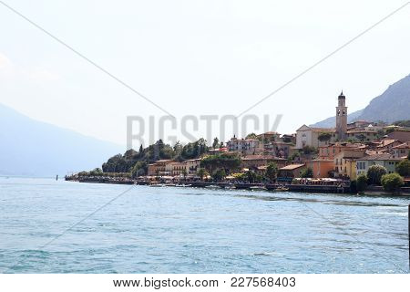 Townscape Panorama Of Lakeside Village Limone Sul Garda With Boats And Church At Lake Garda, Italy