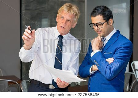 Executive Pointing At Something Out Of Window And Showing Document To Manager. Senior Leader Consult