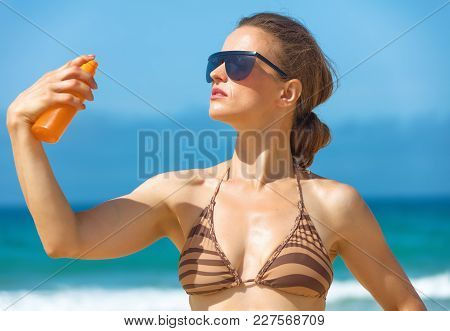 Young Woman On Seashore Applying Sun Cream