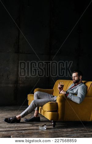 Fashionable Man With Glass Of Whiskey Sitting On Couch With Cigar In Ashtray On Floor