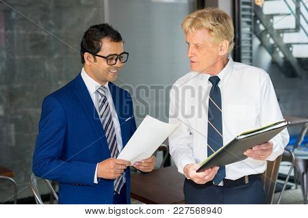 Senior Businessman Holding Folder And Talking To Young Partner. Smiling Assistant Giving Contract To