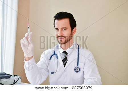 Smiling Doctor Posing In The Office, He Is Wearing A Stethoscope, Medical Staff On The Hospital Back