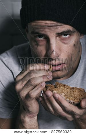 Homeless poor man eating piece of bread