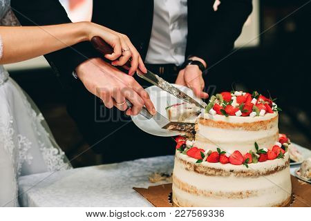 Hands Of The Bride And Groom Cutting Wedding Cake Knife