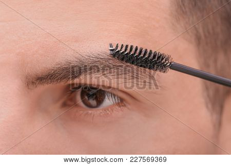 Young man correcting shape of eyebrows, closeup