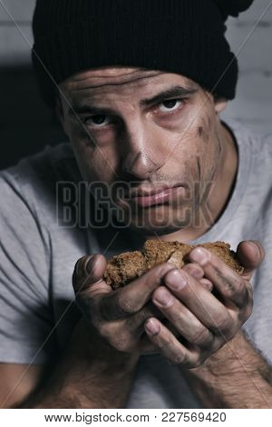 Homeless poor man with piece of bread
