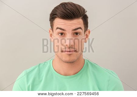 Young man with raised eyebrows on light background