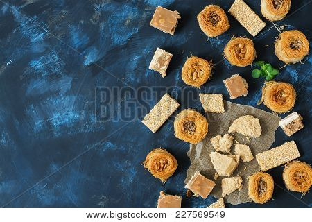 Oriental Sweets, Baklava, Halva, Sesame With Honey, Sherbet On A Blue Background. Top View, Space Fo
