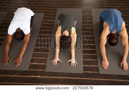 Group Of Three Young Sporty Afro American And Caucasian People Practicing Yoga Lesson Stretching In