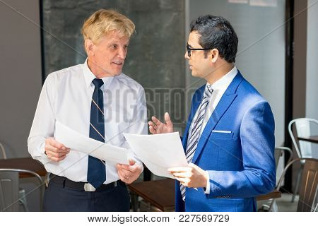 Two Businessmen Holding Documents And Talking. Business Partners Discussing Contract Condition. Busi