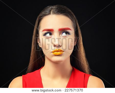 Young woman with dyed eyebrows and creative makeup on black background