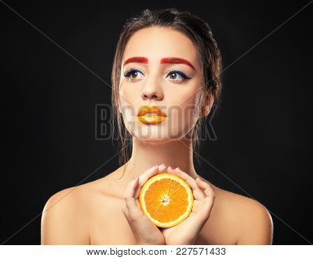 Young woman with dyed eyebrows and half of orange on black background