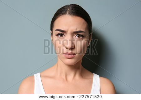 Young woman frowning her eyebrows on color background