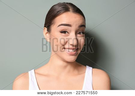 Young woman raising her eyebrows on color background