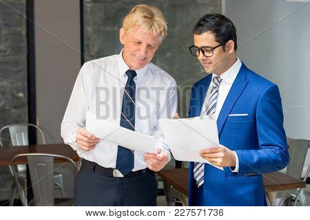 Two Businessmen Reviewing Contract Or Cost Sheet. Partners Meeting For Closing Deal. Business Meetin