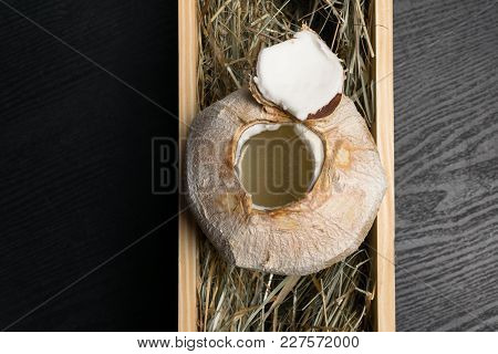 Coconut With Coco Milk In The Hay Background