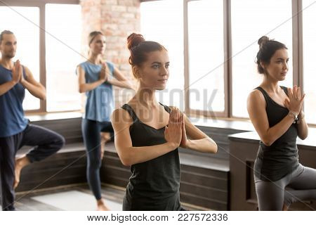 Group Of Young Sporty People Practicing Yoga Lesson Standing In Vrksasana Exercise, Tree Pose With N