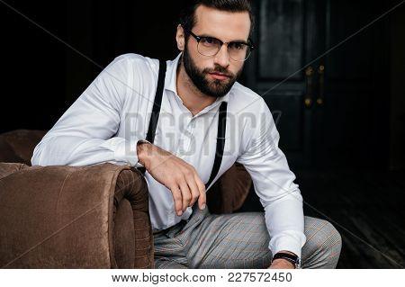 Handsome Elegant Man In Eyeglasses, White Shirt And Suspenders Sitting In Armchair