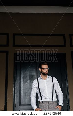 Handsome Bearded Man Posing In White Shirt And Suspenders Against Door