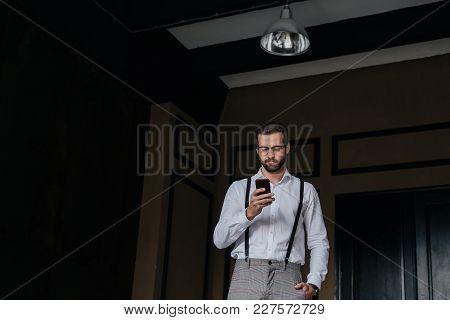 Elegant Bearded Man In Suspenders Using Smartphone