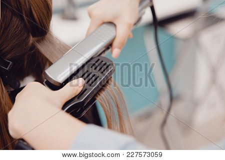 Close Up Of Hands Of Professional Hairdresser Beauty Salon, Straighteners Curling Female Hair