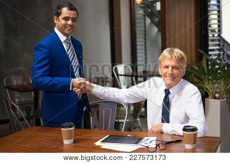 Young And Senior Men In Ties And White Shirts Handshaking At Desk With Coffee, Documents And Tablet.