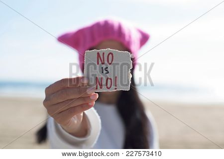 closeup of a young caucasian woman outdoors wearing a pink pussycat hat showing a piece of paper in front of her face with the text no is no written in it
