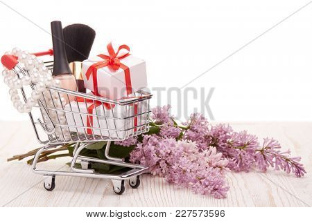 Shopping trolley with gift boxes and brenches of Lilac on a wooden table on white background with copy space. Greeting card. Mothers day, Women's day, valentine's day, birthday.