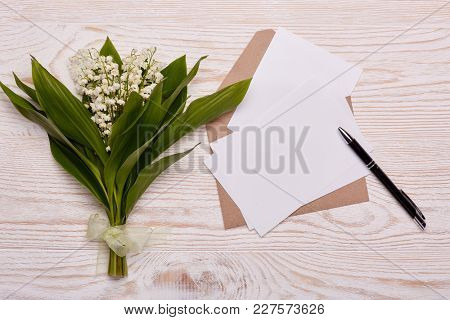 Blank sheets with envelope  and bouquet of Lilies of the valley on a  white  wooden background. Top view. Copy space. Greeting card. Mothers day, Women's day, valentine's day, birthday.