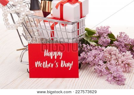 Shopping trolley with gift boxes and brenches of Lilac on a wooden table on white background. Greeting card. Mothers day.