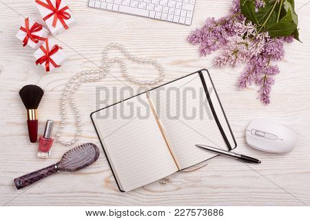 Trendy woman's desk with blank notepad for text, computer keyboard and mouse, gifts, jewelry,cosmetics and lilac flowers on ligth wooden background. Top view. Mockup.