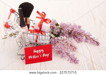 Shopping trolley with gift boxes and brenches of Lilac on a wooden background. Greeting card. Mothers day. Top view.