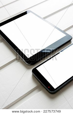 Empty Generic Tablet Pc And Mobile On Top Of White Wood, Vertical
