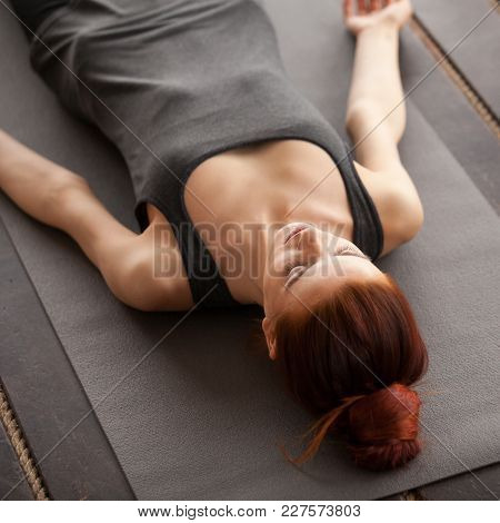 Young Attractive Woman Lying In Dead Body Or Corpse Pose, Savasana Exercise, Resting After Working O
