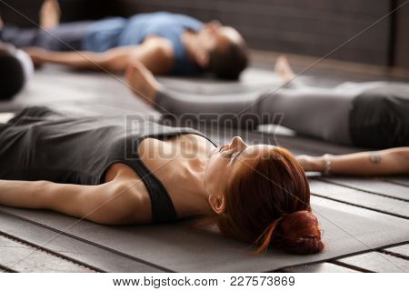 Group Of Young Sporty People Practicing Yoga Lesson Lying In Dead Body Or Corpse Pose, Savasana Exer