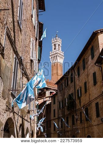 View On The Torre Del Mangia From One Of The Streets Leading Up To The Piazza Del Campo In Siena, It