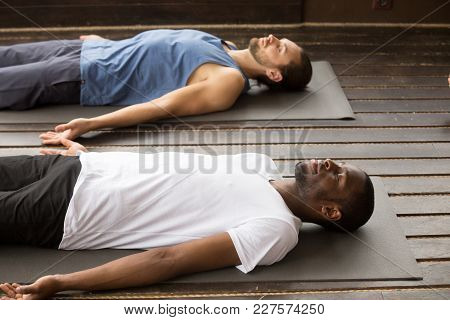 Group Of Two Young Afro American And Caucasian Sporty People Practicing Yoga Lesson Lying In Dead Bo