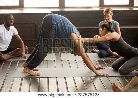 Female Instructor Helping Male Student With Downward Facing Dog Exercise, Teaching Adho Mukha Svanas