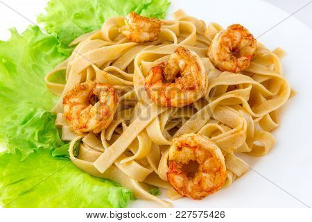 Boiled Pasta With Fried Shrimp. Tagliatelle Macaroni Are Observed With Fried Langoustines And Lettuc