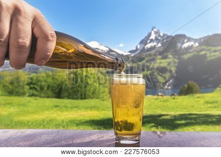 Glass Of Beer And Summer Alpine Landscape - Hand Of A Man Pouring Beer From A Bottle In A Glass With