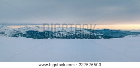 Winter mountain landscape with cloudy sky, lit by the sunset. Panoramic photo.