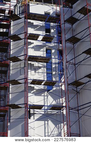 Construction Of A New Church In A Modern Style. Scaffolding Around The White Walls Of The Church. Ne