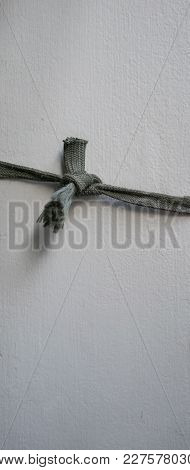 Old Fabric Rope Tightly Tied In Knot Isolated On Grey Wall. Overused And Worn Out Concept.