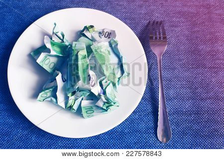 Crumpled Money On A Plate, Blue Background