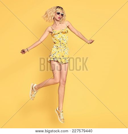 Happy Girl Jumping In Studio On Yellow Background. Blond Slim Model Having Fun In Fashionable Sungla