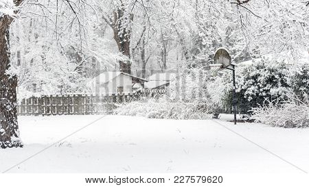 Basketball Backboard Covered In Snow In Yard With Fence And Shack In The Background