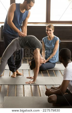 Yoga Instructor Helping Fit Sporty Young Woman Performing Bridge Exercise, Pilates Trainer Assisting