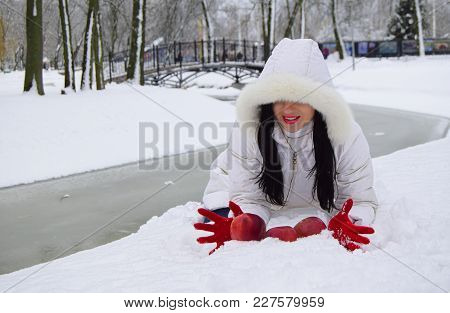 The Young Woman The Brunette Has Placed Red Apples On Snow In A Snowdrift. The Woman Is Dressed In R