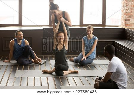Female Instructor Helping Woman To Stretch Teaching Flexibility In Cow Face Gomukhasana Pose At Grou